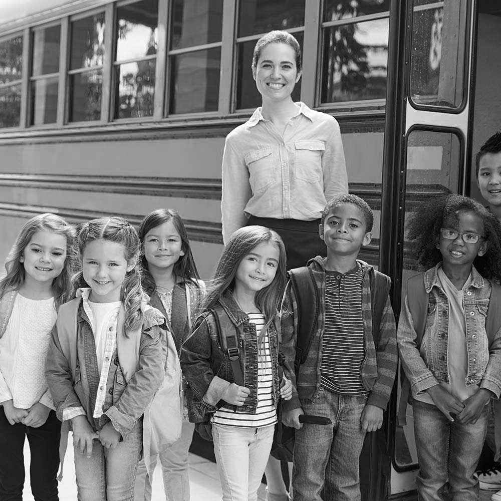 elementary-school-teacher-and-pupils-standing-by bus